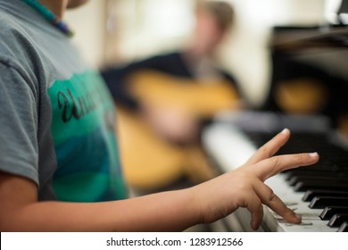 Young boy learning to play the piano while his older brother plays guitar in the background.