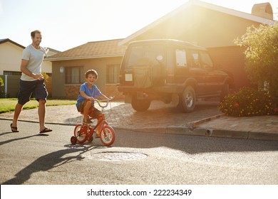 young boy learning to ride bicycle as father teaches him in the suburb street having fun.