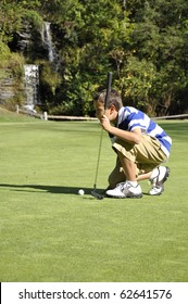 Young boy lining up a shot on a golf course.