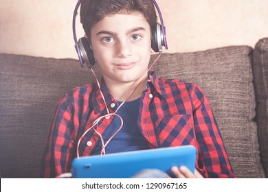 Young boy listening to his favorite music using his tablet. Kids and technology concept