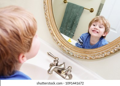 Young boy looking in bathroom mirror after pretending to shave a