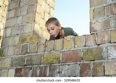 Young boy is looking down over a brick wall, exploring a pit, low angle view