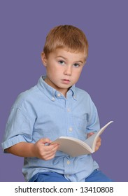 Young boy looking up from his book