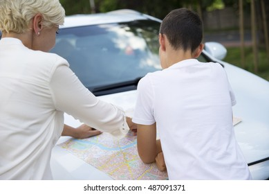 Young boy looking at a map with his mother