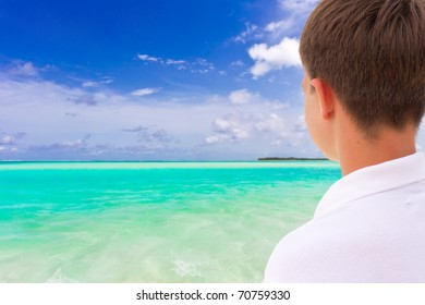 Young boy looking out over a tropical seascape in the Maldives.