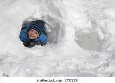 Young boy looking out from a snow cave