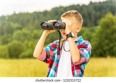 Young boy looking through binoculars, outdoors