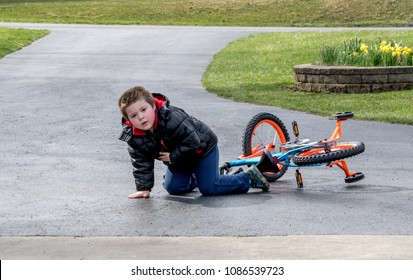 a young boy looks up from falling off his first bike. im ok!