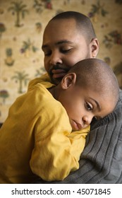 Young boy is lovingly being held by his father.  Vertical shot.