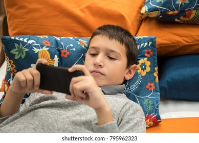 Young boy lying in the bad with mobile phone in his hands, watching, texting, focused