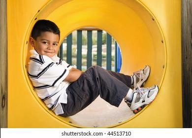 Young boy lying in crawl tube at playground. Horizontally framed shot.