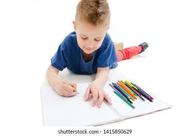 Young boy lying on floor with pencils on a sketch book with a look of concentration, close up view. Isolated on white background