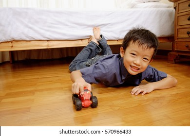 Young boy lying on floor with toy car, looking at camera