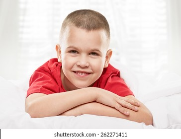 Young boy lying on his bed smiling at the camera. light window background