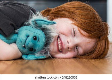 Young boy lying on the kitchen floor playing with a generic stuffed goblin toy his grandmother made for him, in Reno, Nevada, USA