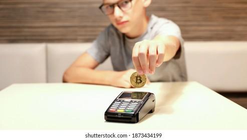 Ein kleiner Junge leistet eine Zahlung mit Kryptowährungen. Nutzung der digitalen Währung gegen Bezahlung. Illustrative Bitcoin-Zahlung.
