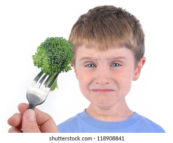 A young boy is making a funny disgusting face at a fork with a healthy piece of broccoli on a white background.