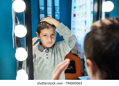 Young boy making hairstyle in front of the mirror