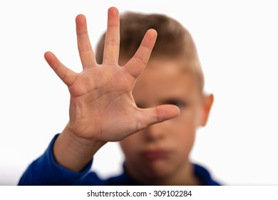 Young boy making stop gesture with his hand. Focus is on the hand. The face of the boy is blurred.