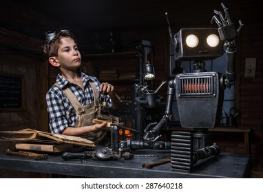 Young boy mechanic starts the robot in his workshop
