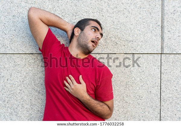 young boy millennials making funny expressions, comic and grotesque portrait of boy with wall background