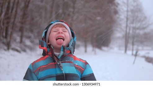 Young boy in the morning when it's snowing.