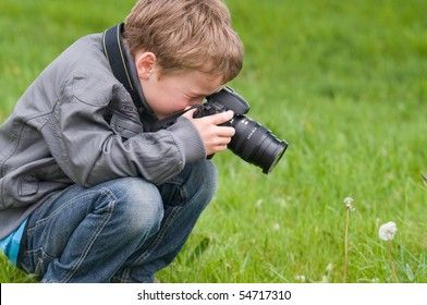 Young boy, nine years old, already practicing with an SLR shooting pictures of nature.