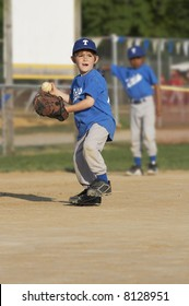 young boy on a baseball field with ball in hand