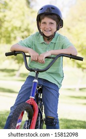 Young boy on bicycle outdoors smiling
