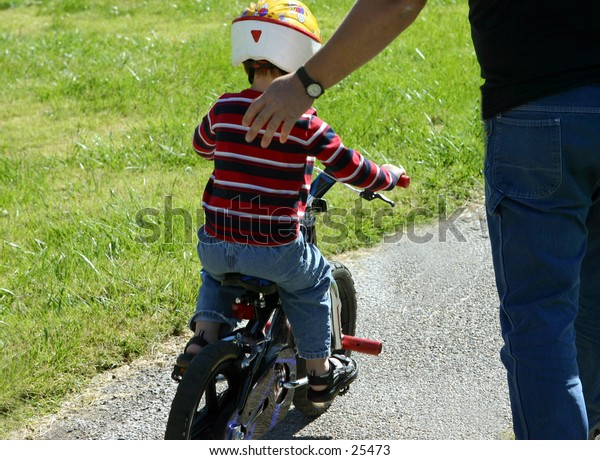 Young boy on his bike with help