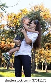 Young boy on mother's arms at park