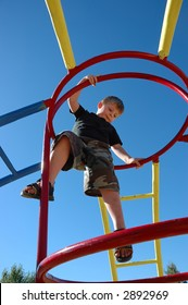 Young boy on playstructure with deep blue sky.