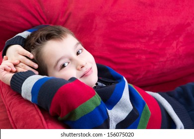 Young boy on the red couch comfortably relaxing and looking at you with confidence, perhaps he has been counseling by psychiatrist