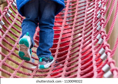 Young boy on a rope climbing frame