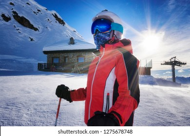 young boy on ski slope with goggles and reflection of snowed mountains on the mask. Portrait of skier at the ski resort with mountain shelter and snow on background