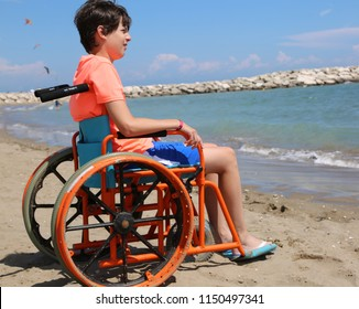 young boy on the special wheelchair with large wheels to move smoothly on the sand of the beach by the sea in summer