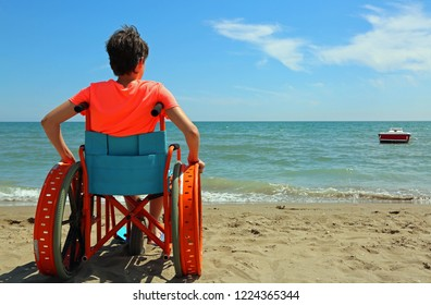 young boy on the special wheelchair with metal wheels on the beach in summer