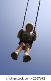 Young boy on swing against dark blue sky