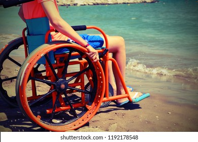 young boy on the wheelchair on the beach with vintage effect