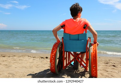 young boy on the wheelchair on the beach during summer holidays