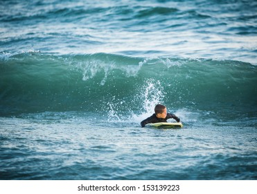 Young boy on a yellow boogie board looking back at a wave about to crash down at Sunset Beach in Southern California