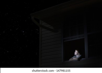 Young boy at open window looking at night sky