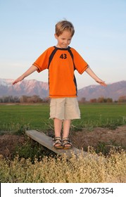 young boy in orange shirt crossing a wood plank over a ditch