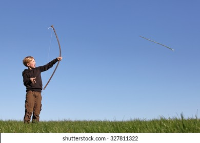 Young boy outdoors with bow and arrow