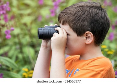 Young boy outside using a pair of binoculars
