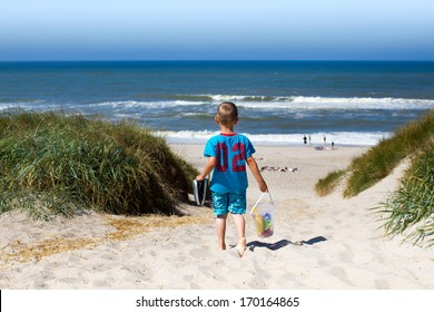 Young boy overlooking horizon over water and walking through eroded sand dunes on his way to a beach in Northern Europe during summer time. Boy is carrying his plastic toys for water play.