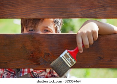 Young boy painting the wooden fence - peeking through the planks
