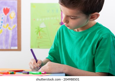 A young boy paints on art lessons