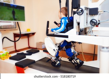 young boy passes robotic gait therapy in rehabilitation center