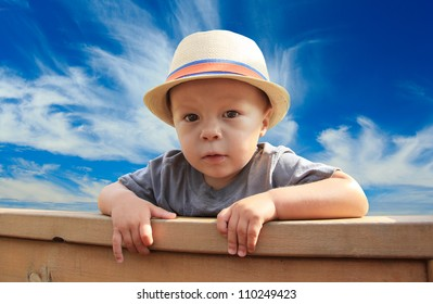 Young boy peeking over a fence.